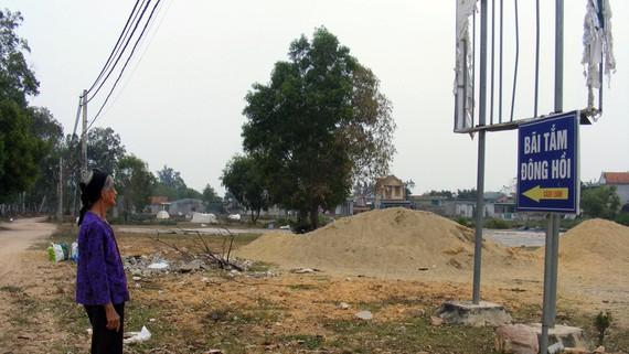 Bà Lê Thị Điện bên tấm bảng quy hoạch Nhà máy nhiệt điện Quỳnh Lập bị rách te tua