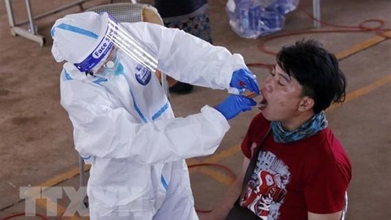 Bác sỹ lấy mẫu xét nghiệm cho một người dân ở Vientiane. Ảnh: TTXVN