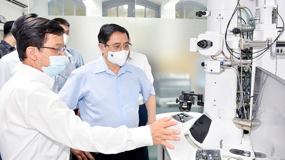 Thủ tướng Phạm Minh Chính tham quan trang thiết bị phục vụ việc nghiên cứu tại Viện Vệ sinh dịch tễ Trung ương. Ảnh: VIẾT CHUNG