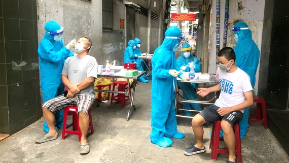 Anh Trần Bình An, sinh viên Trường Đại học Y khoa Phạm Ngọc Thạch (ngoài cùng bên trái) lấy mẫu xét nghiệm cho người dân