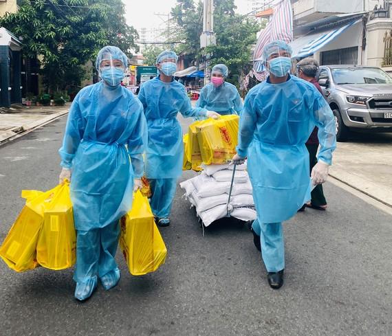 Đoàn viên thanh niên khu phố 1, phường Hòa Thạnh, quận Tân Phú đưa nhu yếu phẩm vào khu phong tỏa, trao tận tay người dân. Ảnh: VŨ TÂN