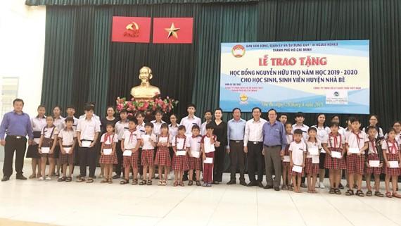Ông Lê Văn Công, Kiểm Soát viênCông ty TNHH Một thành viên Xổ số kiến thiết TP Hồ Chí Minh cùng với lãnh đạo UBMTTQ TP, UBMTTQ huyện Nhà Bè và đơn vị Tài trợ chụp hình lưu niệm cùng với các em học sinh,sinh viên nhận học bổng