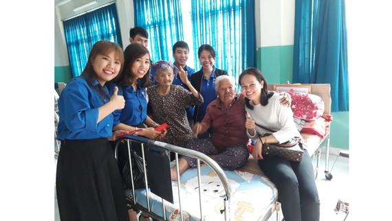 Đoàn công tác của Báo SGGP đến từng giường lì xì  mừng tuổi các cụ ở Trung tâm Nuôi dưỡng bảo trợ người bại liệt Thạnh Lộc
