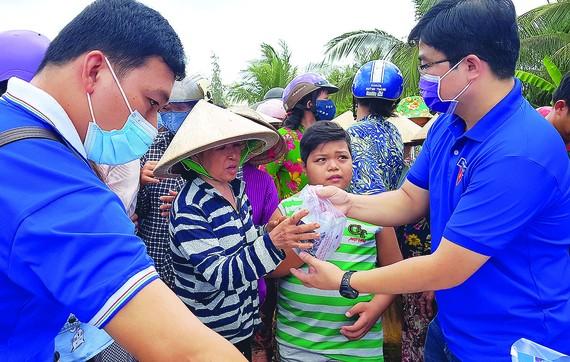 Các bạn trẻ tham gia phát khẩu trang, nước rửa tay sát khuẩn, sổ tay tuyên truyền phòng chống dịch Covid-19 cho bà con xã Thạnh Phú Đông, huyện Giồng Trôm, tỉnh Bến Tre