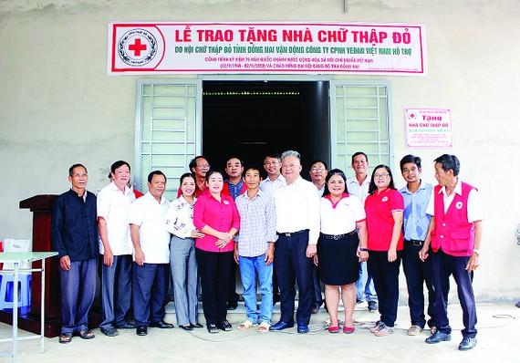 Ông Hwang Fa Jane - đại diện Công ty CPHH Vedan Việt Nam cùng đại diện chính quyền địa phương trong buổi trao tặng nhà cho anh Vi Văn Bé