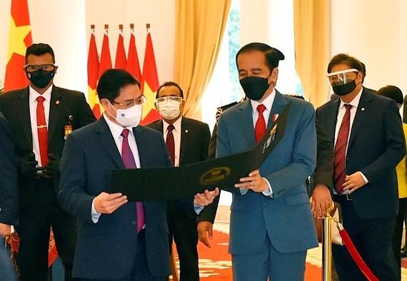 Tổng thống Indonesia Joko Widodo thân tặng Thủ tướng Phạm Minh Chính tấm hình kỷ niệm cuộc gặp đầu tiên trên cương vị Thủ tướng. Ảnh: VGP