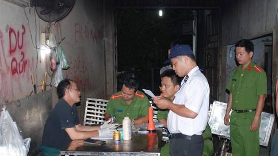 Lực lượng công an lập biên bản cơ sở giết mổ heo không đảm bảo vệ sinh an toàn thực phẩm.