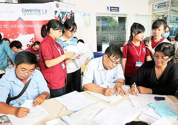 Thí sinh làm thủ tục nhập học ngày 1-8 tại Trường ĐH Nguyễn Tất Thành. Ảnh: THANH HÙNG