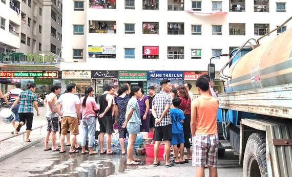 Người dân tại nhiều khu vực ở Hà Nội phải xếp hàng chờ lấy nước từ xe bồn  vì nước sạch sông Đà nhiễm mùi lạ. Ảnh: QUỐC KHÁNH