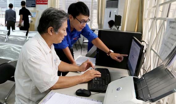Công chức UBND quận Bình Thạnh hướng dẫn người dân  thực hiện đăng ký hồ sơ qua mạng. Ảnh: Thái Phương