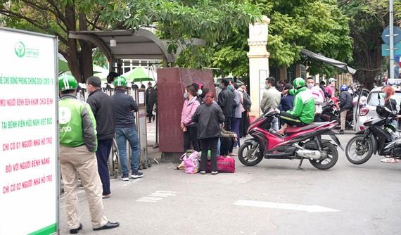 Mặc dù dịch bệnh phức tạp, nhưng trước cổng Bệnh viện Hữu nghị Việt Đức luôn có nhiều người tập trung. Ảnh: ĐỖ TRUNG