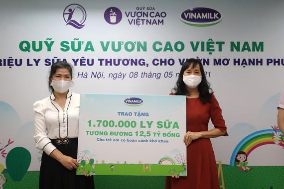 Đại diện Vinamilk trao bảng tượng trưng 1,7 triệu ly sữa của Quỹ sữa Vươn cao Việt Nam cho Đại diện Quỹ bảo trợ trẻ em Việt Nam