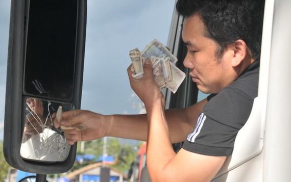 Một tài tài xế xe Container đưa tiền lẻ tại trạm thu phí chiều 14-8 - Ảnh: THANH TÚ