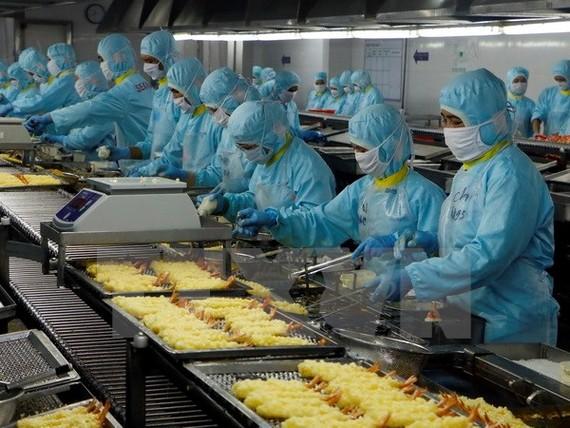 Chiên tôm tempura trong nhà máy Seavina. (Ảnh: Thanh Liêm/TTXVN)