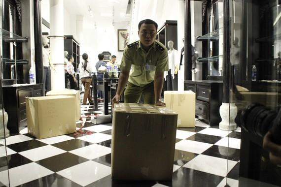 Lực lượng quản lý thị trường niêm phong hơn 1.000 sản phẩm lụa Khaisilk tại cửa hàng trên đường Đồng Khởi - Ảnh: NGUYỄN TRÍ