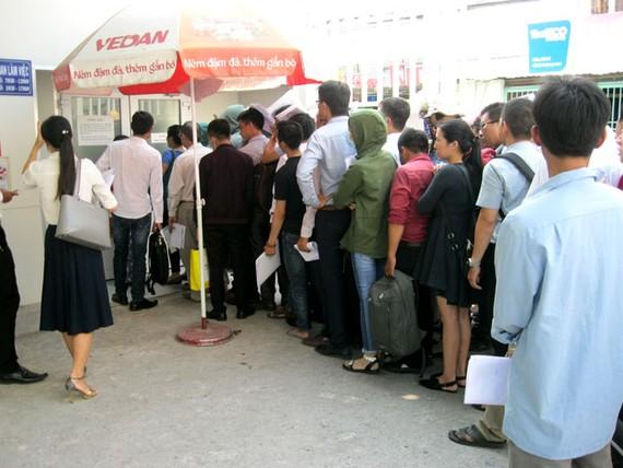 Mặc dù chưa đến giờ mở cửa, nhưng rất đông người dân chờ đợi nộp hồ sơ cập nhật biến động nhà, đất tại Chinh nhánh Văn phòng đăng ký Đất đai quận 9 vào trưa ngày 13-4.