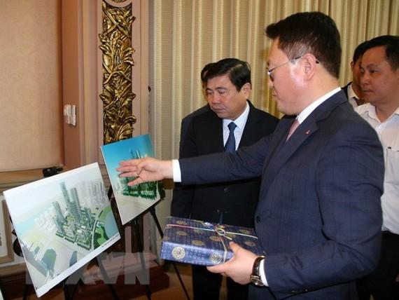 Chủ tịch UBND Thành phố Hồ Chí Minh Nguyễn Thành Phong và Tổng Giám đốc Điều hành Công ty Lotte Asset Development Lee Kwang Young trao đổi về phối cảnh dự án. (Ảnh: Tiến Lực/TTXVN)