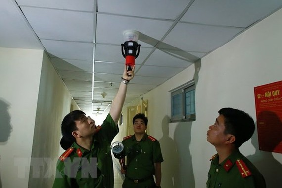 Cảnh sát phòng cháy, chữa cháy kiểm tra hệ thống báo cháy tại chung cư HH Linh Đàm. (Ảnh: TTXVN)