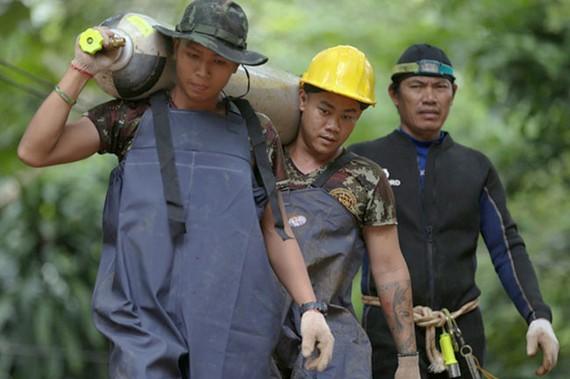 Binh sĩ Thái vận chuyển các bình dưỡng khí đã hết từ trong hang ra ngoài - Ảnh: REUTERS