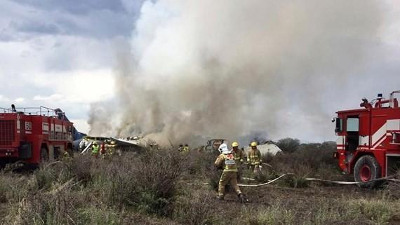 Nhân viên cứu hộ và cứu hỏa tại hiện trường máy bay chở khách Embraer của hãng Aeromexico rơi gần sân bay Durango, Mexico, ngày 31-7-2018. Ảnh do Cơ quan Phòng vệ Dân sự bang Durango công bố