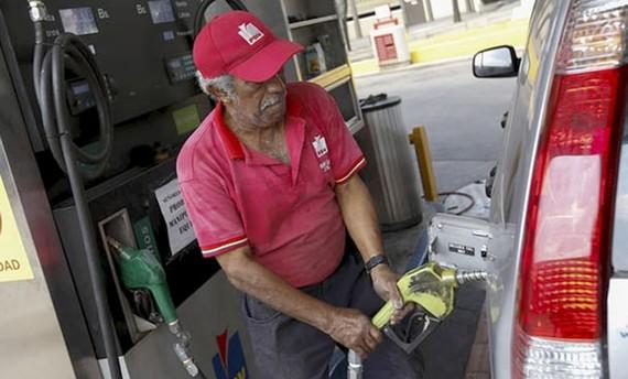 Một công nhân đang bơm nhiên liệu cho xe tại một trạm xăng ở Caracas, Venezuela. Ảnh: Marco Bello/Reuters