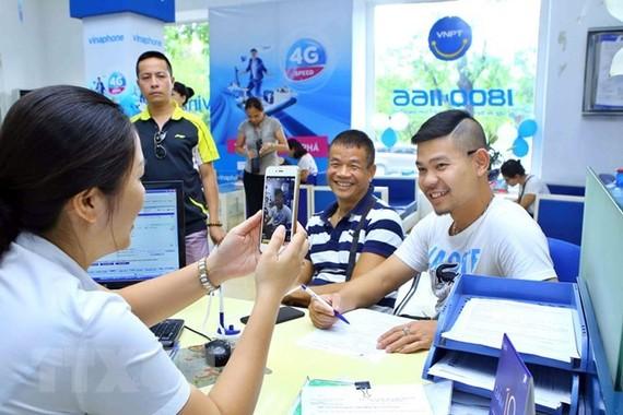 Nhân viên chụp ảnh chân dung khách hàng đến đăng ký thuê bao trả trước mới tại Trung tâm kinh doanh VNPT Vinaphone Hà Nội. (Ảnh: Minh Quyết/TTXVN)