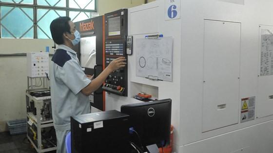 Vận hành máy CNC tạo sản phẩm cơ khí chính xác tại Công ty Nhựa Duy Tân. Ảnh: CAO THĂNG