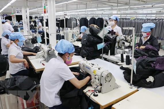 Công nhân đang sản xuất hàng may mặc. (Ảnh: Trần Lê Lâm/TTXVN)