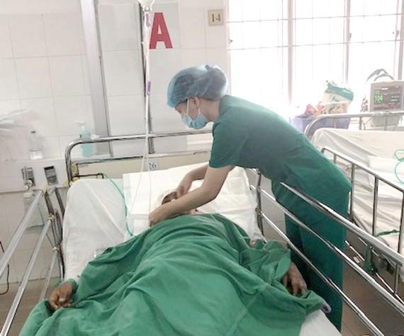 Các bác sĩ chăm sóc cho bệnh nhân sau phẫu thuật thành công