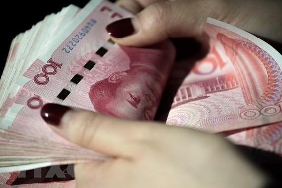 Kiểm đồng Nhân dân tệ tại Bắc Kinh, Trung Quốc. (Nguồn: AFP/TTXVN)