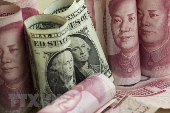 Đồng nhân dân tệ và đồng USD tại một ngân hàng ở Bắc Kinh, Trung Quốc. (Nguồn: AFP/TTXVN)