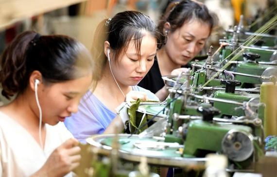 Công nhân làm việc tại một dây chuyền may quần áo xuất khẩu ở tỉnh Hà Nam của Trung Quốc. (Ảnh: AFP/TTXVN)