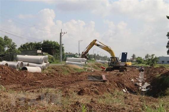 Thi công đường công trình thoát nước phục vụ dân sinh tại Tiền Giang. (Ảnh: Minh Trí/TTXVN)
