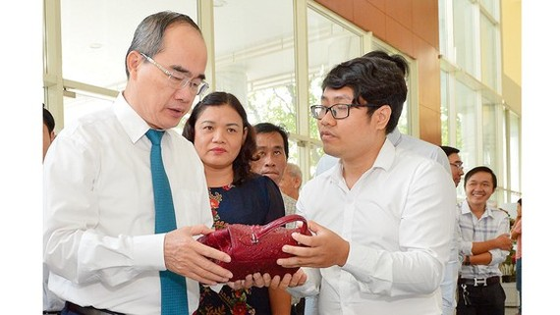 Bí thư Thành ủy TPHCM Nguyễn Thiện Nhân xem triển lãm các sản phẩm thủ công mỹ nghệ của hợp tác xã tại hội nghị. Ảnh: VIỆT DŨNG