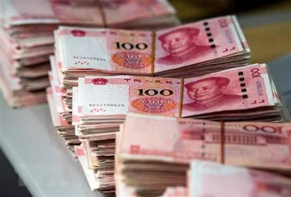 Đồng tiền mệnh giá 100 nhân dân tệ tại Thượng Hải, Trung Quốc. (Nguồn: AFP/TTXVN)