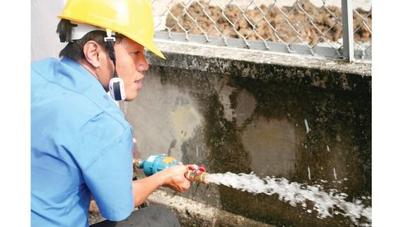 Nhân viên Tổng Công ty Cấp nước Sài Gòn kiểm tra chất lượng nước tại đồng hồ của khách hàng. Ảnh: MINH PHONG