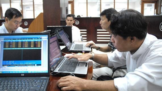 Nhà đầu tư theo dõi giá cổ phiếu. Ảnh: THÀNH TRÍ