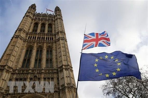 Quốc kỳ Anh (phía trên) và cờ Liên minh châu Âu (phía dưới) bên ngoài tòa nhà Quốc hội Anh ở London. (Nguồn: THX/TTXVN)