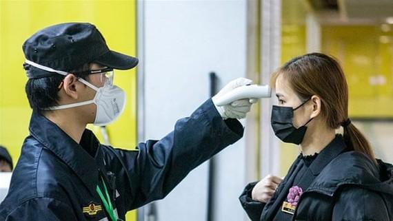 Kiểm tra thân nhiệt để phòng chống dịch virus corona. (Nguồn: EPA)