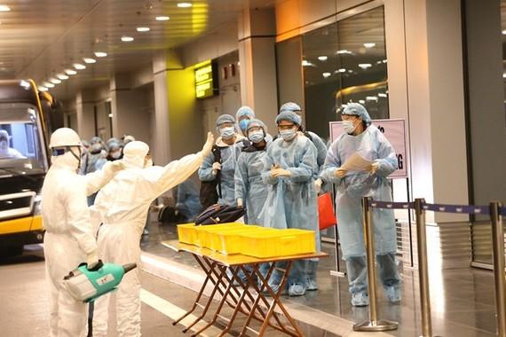 Công dân Việt Nam được khử trùng trước khi làm thủ tục nhập cảnh tại sân bay Vân Đồn (Quảng Ninh). (Ảnh: Dương Giang/TTXVN)