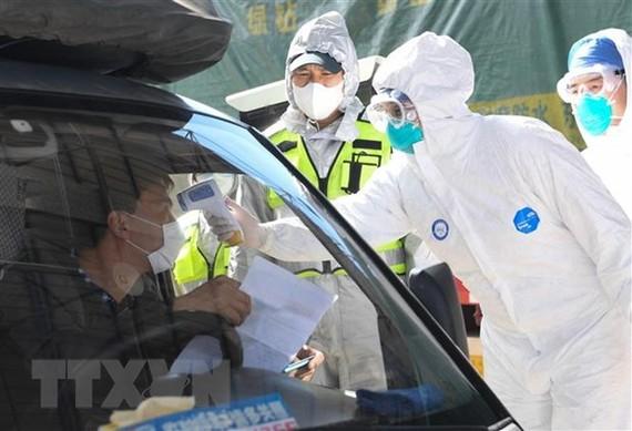 Kiểm tra thân nhiệt cho một tài xế tại Chiết Giang, Trung Quốc ngày 8/2/2020. (Ảnh: THX/TTXVN)