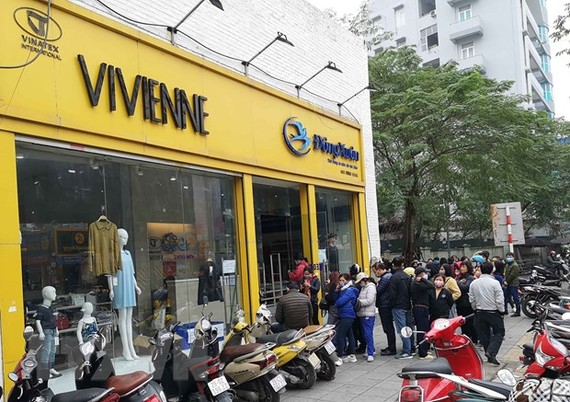 Người dân xếp hàng mua khẩu trang của Công ty Dệt kim Đông Xuân. (Ảnh: Thanh Tùng/TTXVN)