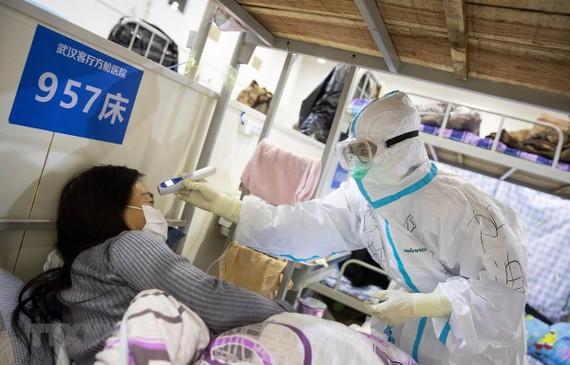 Nhân viên y tế kiểm tra thân nhiệt một bệnh nhân nghi nhiễm COVID-19. (Ảnh: AFP/TTXVN)