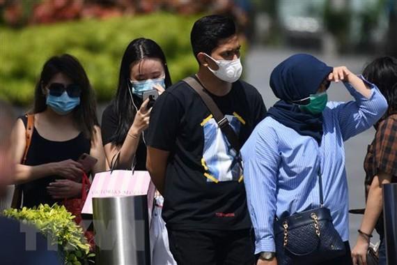Người dân đeo khẩu trang phòng dịch viêm đường hô hấp cấp do virus COVID-19 tại Singapore. (Ảnh: AFP/TTXVN)