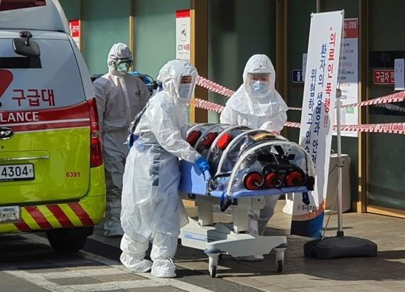 Nhân viên y tế chuyển bệnh nhân nghi nhiễm COVID-19 tới một bệnh viện ở Daegu, Hàn Quốc. (Ảnh: AP)