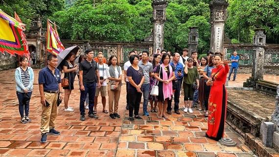Du khách Việt thăm quan đi tích lịch sử trong quần thể danh thắng Tràng An. (Ảnh: Xuân Mai/Vietnam+)