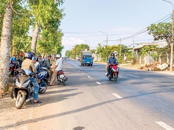 Cò đất tập trung hai bên Quốc lộ 56 chèo kéo khách đi đường. Ảnh: MINH TUẤN