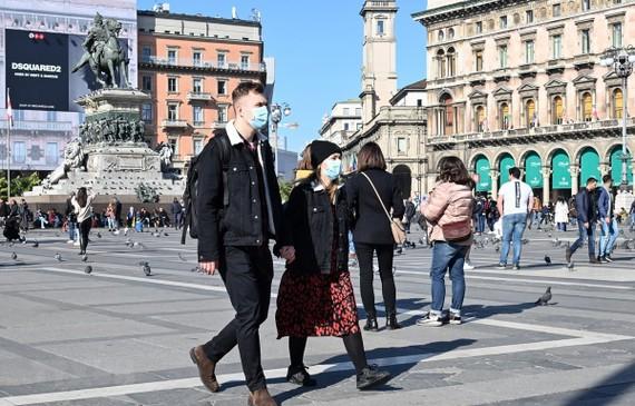 Khách thăm quan đeo khẩu trang phòng dịch COVID-19 tại quảng trường del Duomo, Milan, Italy ngày 24/2/2020. (Ảnh: AFP/TTXVN)
