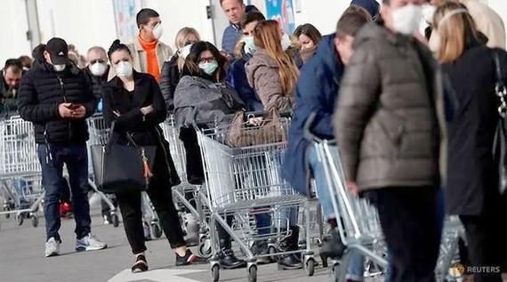 Người dân xếp hàng tại một siêu thị ở miền bắc Italy trong bối cảnh Covid-19 đang lan rộng. Ảnh: REUTERS