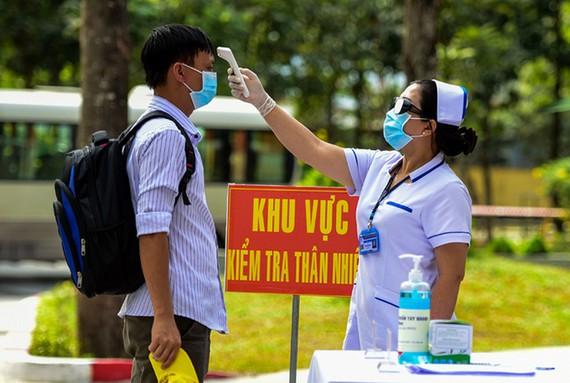 Nhân viên y tế đo thân nhiệt cho người cách ly trong diễn tập đón 550 người tại bệnh viện dã chiến TP HCM. Ảnh:Quỳnh Trần